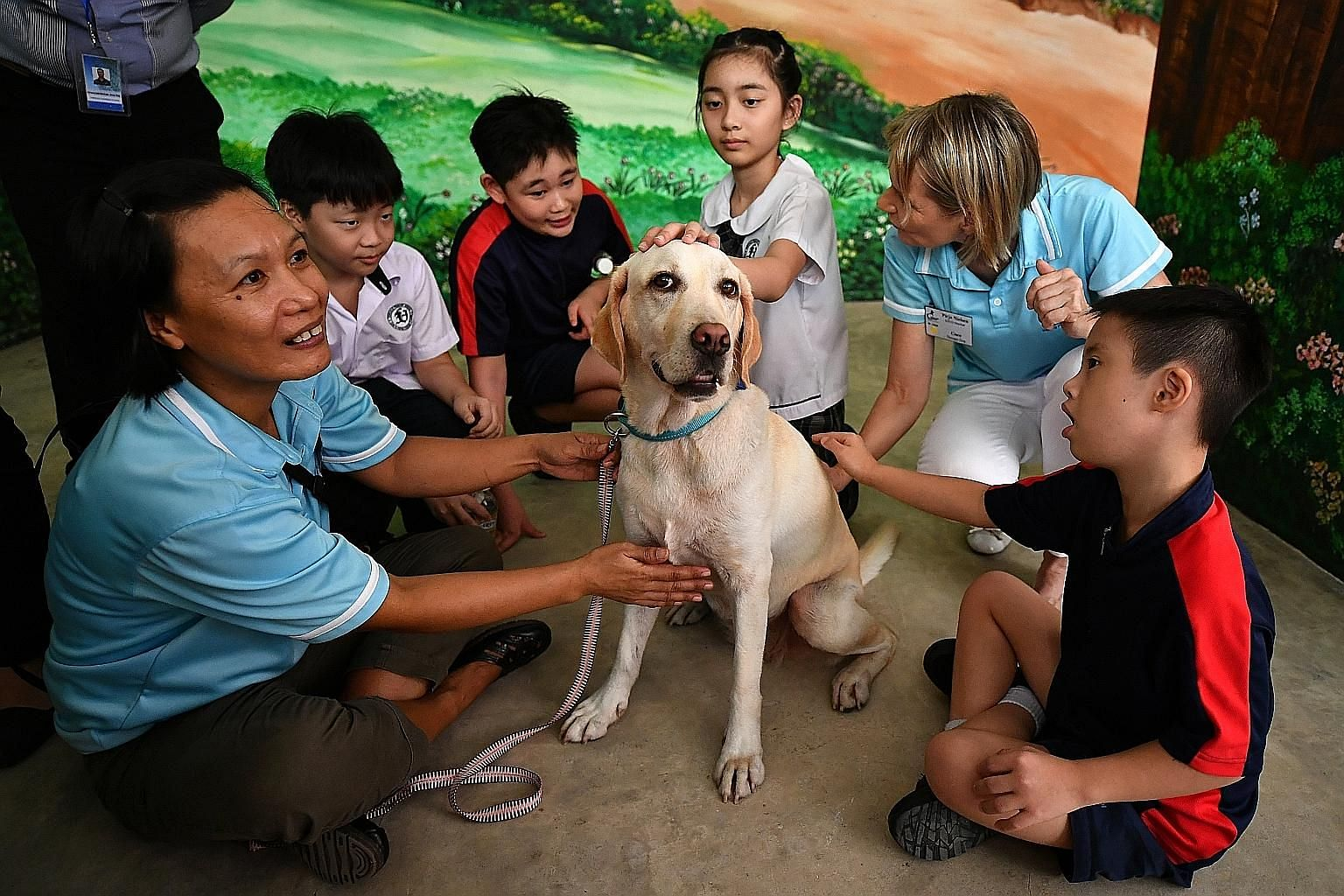 Pupils of Fernvale Primary School and Fernvale Gardens School with therapy dog Baloo and members of Therapy Dogs Singapore yesterday. In line with the plot of the first book (above) in the series, therapy dogs were brought to the book launch for stud