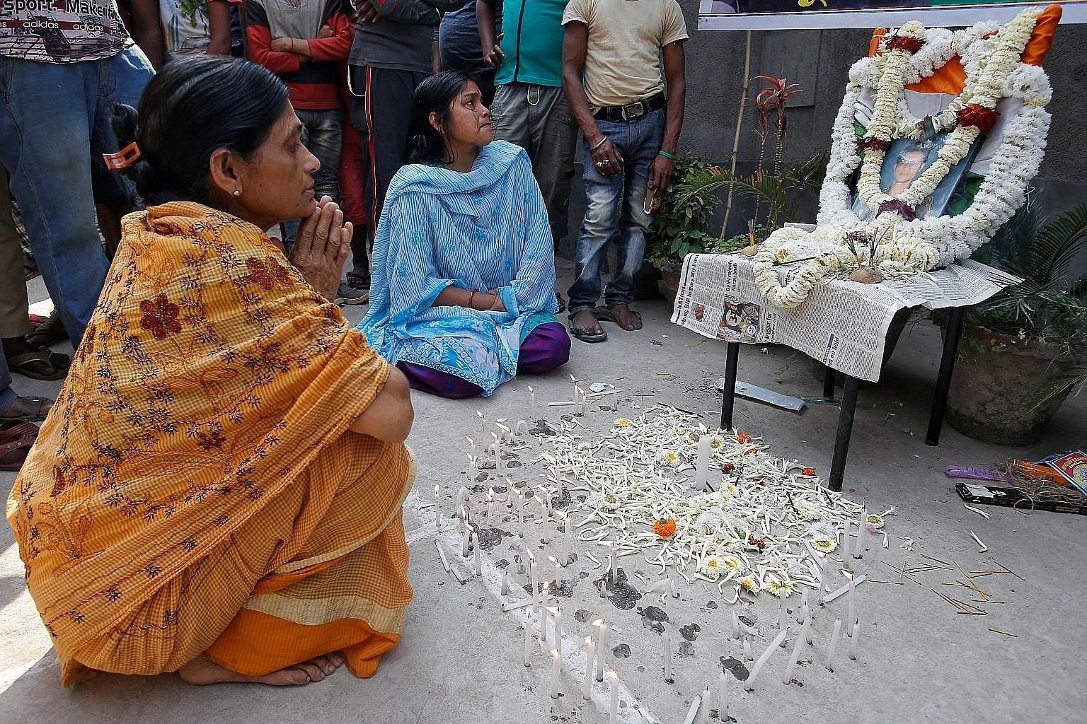 Women praying in front of a portrait of Central Reserve Police Force officer Bablu Santra, who was killed in the Kashmir terror attack.