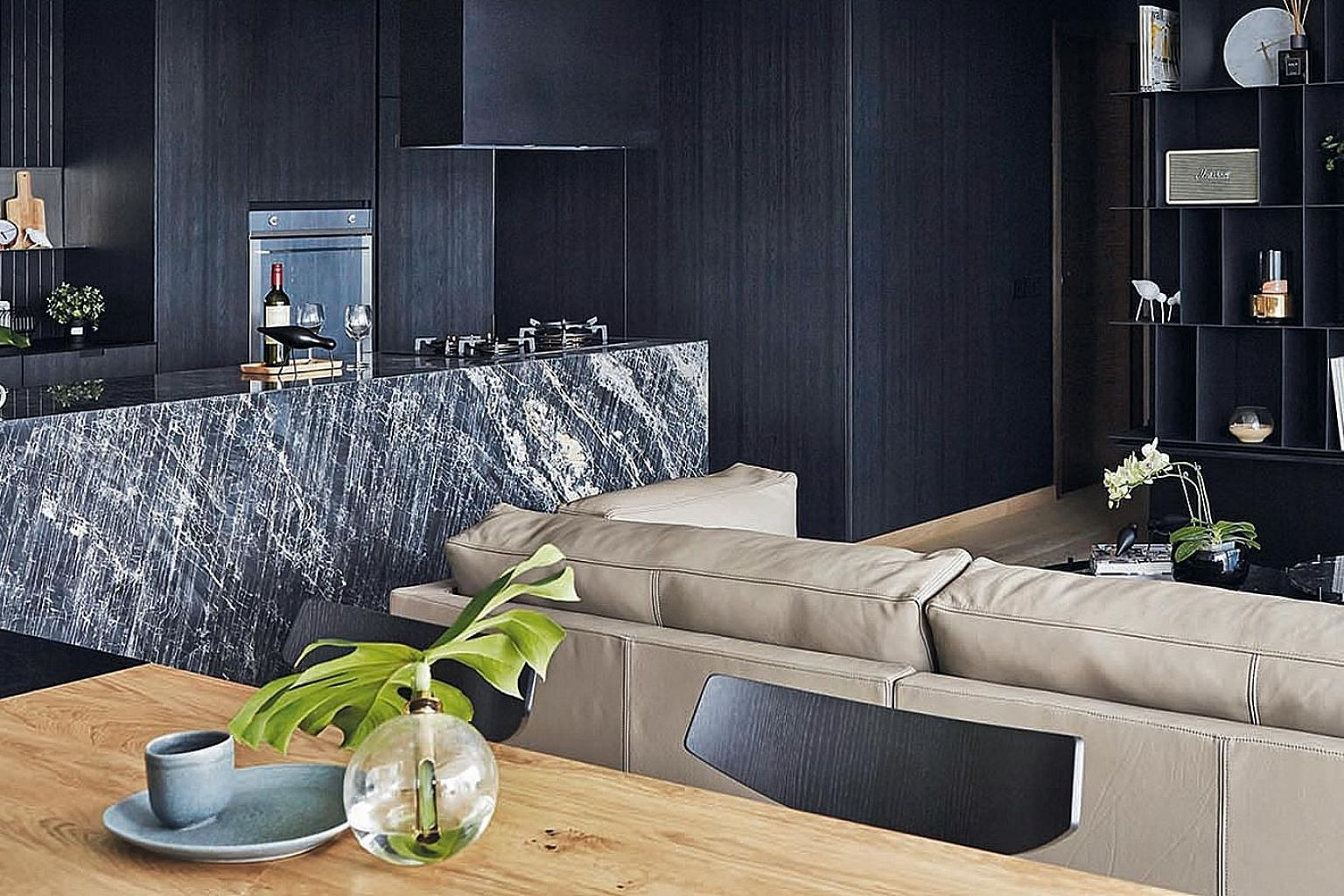 Wood furniture, such as the Bolia Bird dining chairs, as well as plants give the home pops of colour. The colour black is seen throughout the home, such as on the feature walls in the living room (above) as well as kitchen cabinets (top).