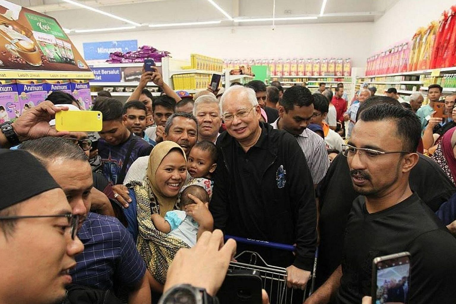 Former Malaysian prime minister Najib Razak having a picture taken with supporters while shopping at Tesco hypermarket in Semenyih on Wednesday. Najib seems to be enjoying new-found popularity despite facing dozens of charges linked to graft and fina