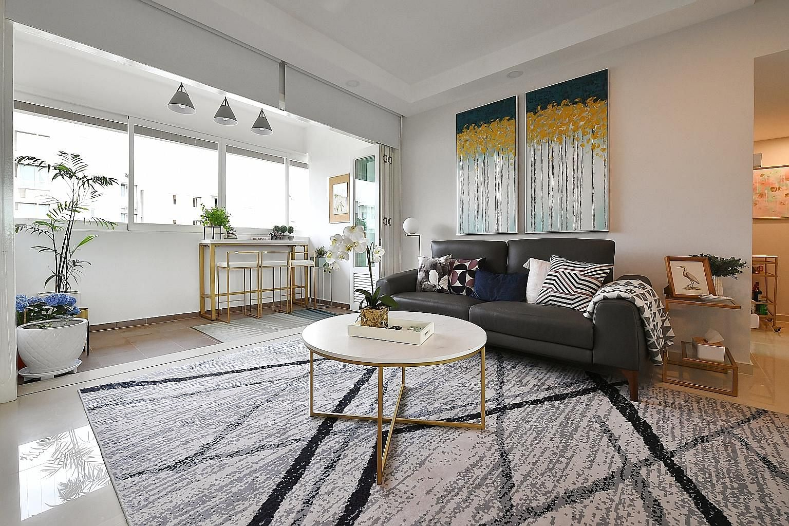 Zen and his sister, Zigsa - both children of entrepreneurs Joanne Huynh and Dorjee Sun - get their own play area in the living room of their four-bedroom condominium in Robertson Quay. While after-dinner drinks are held on the balcony (far left) of t