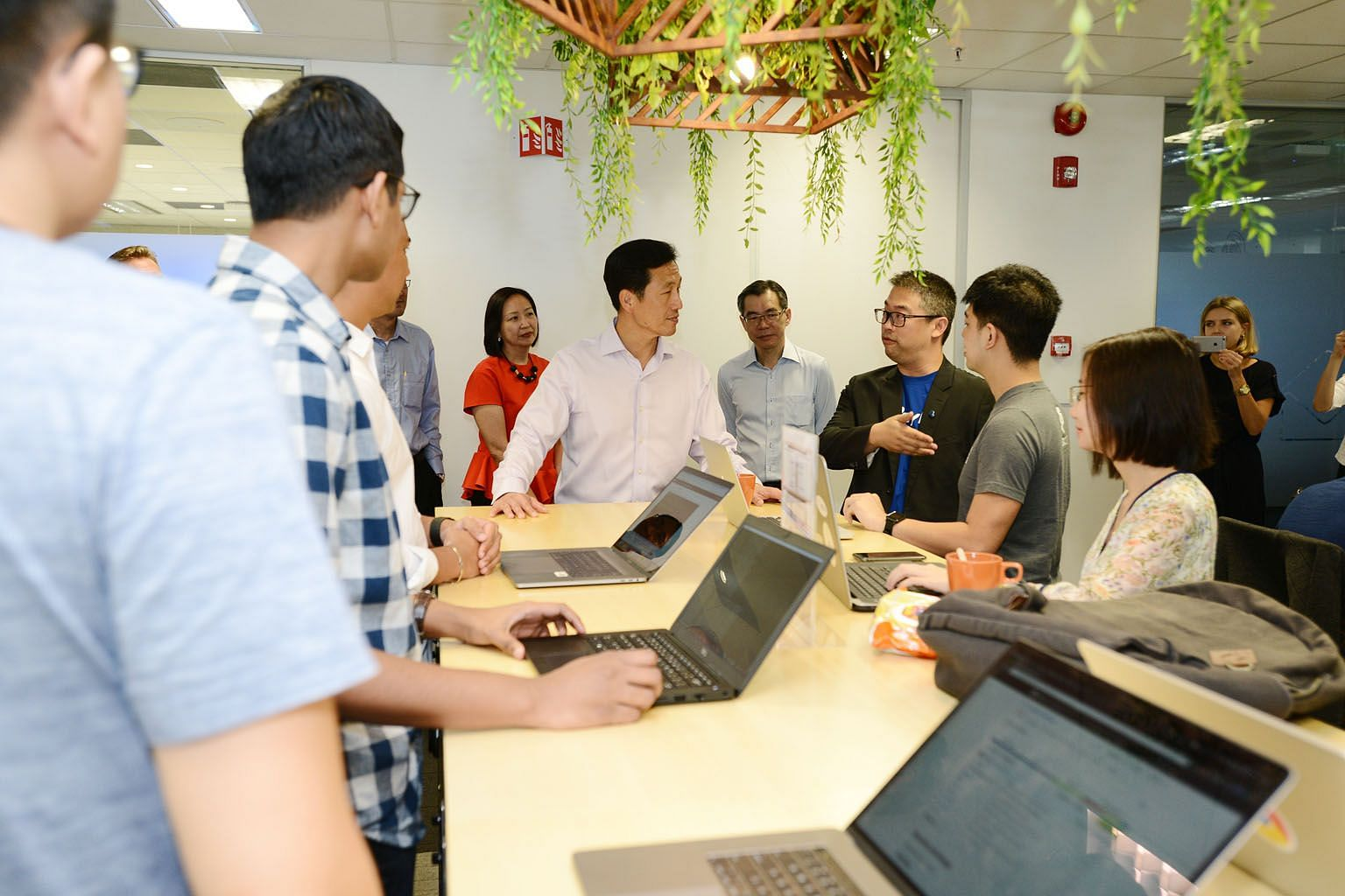 Education Minister Ong Ye Kung (centre) speaking to a PayPal employee at its international headquarters in Singapore. The American company is partnering with tertiary institutes in a programme where students will learn to apply PayPal's payment solut
