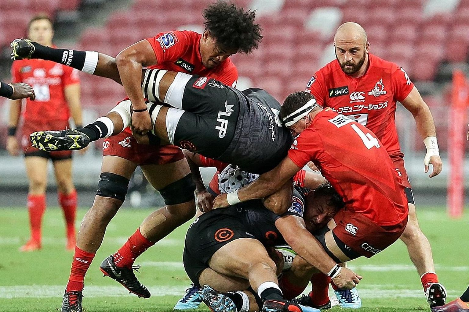 Sunwolves flanker Hendrik Tui (left), lock Luke Thompson (centre) and hooker Jaba Bregvadze (second right) tackling the Sharks players during their Super Rugby match at the National Stadium last night. The Sharks won 45-10.