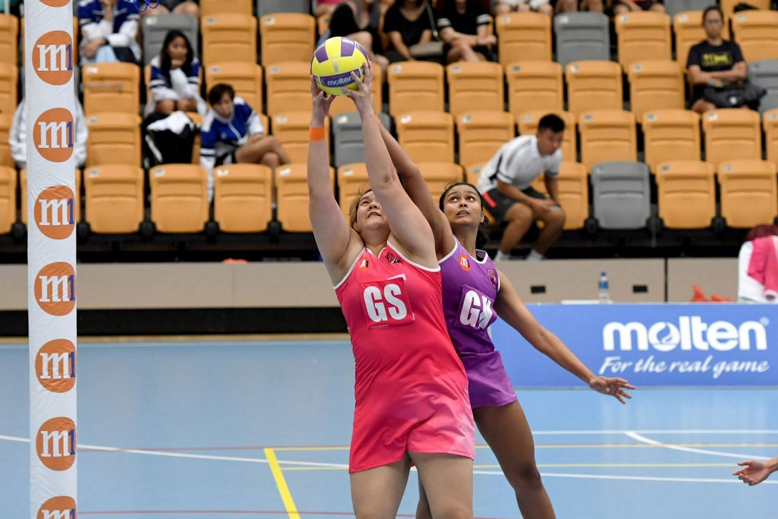Sneakers Stingrays goalkeeper Reena Divya Manogaran challenging Blaze Dolphins goal shooter Lee Pei Shan for the ball in the opening match of the Netball Super League 2019 at Our Tampines Hub yesterday. The Stingrays won 46-45.