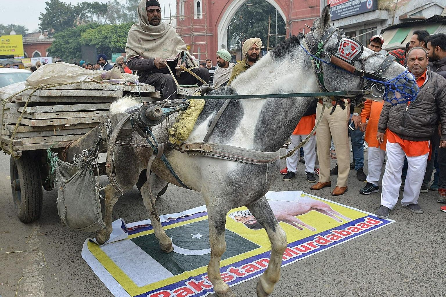 Far left: An Indian man in Amritsar, India, riding his cart over a banner depicting the Pakistani flag and an image of the leader of Pakistan-based Islamist militant group Jaish-e-Mohammad, which claimed responsibility for the car bomb attack last Th