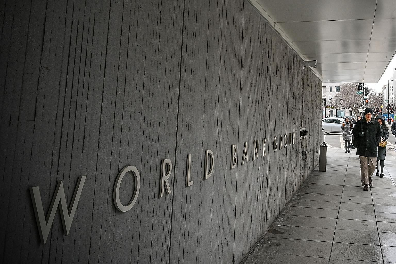 Pedestrians walking past the World Bank building in Washington. To stay relevant, the World Bank needs to move beyond being a lender for development by coupling financing with its skills and expertise in today's most pressing problems of rapid urbani
