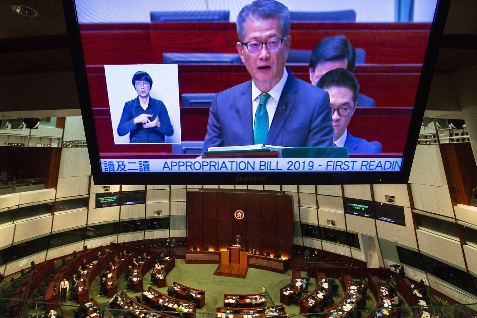 A TV screen showing Hong Kong Financial Secretary Paul Chan delivering his Budget speech yesterday to a packed legislature.
