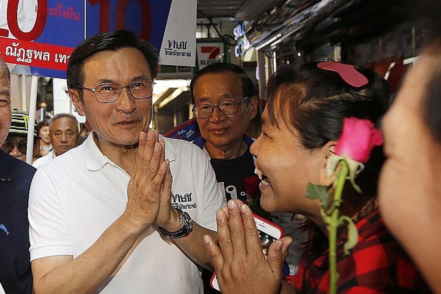 Thai Raksa Chart Party's Chaturon Chaisang (in white T-shirt) greeting people during a campaign event for the country's upcoming general election.