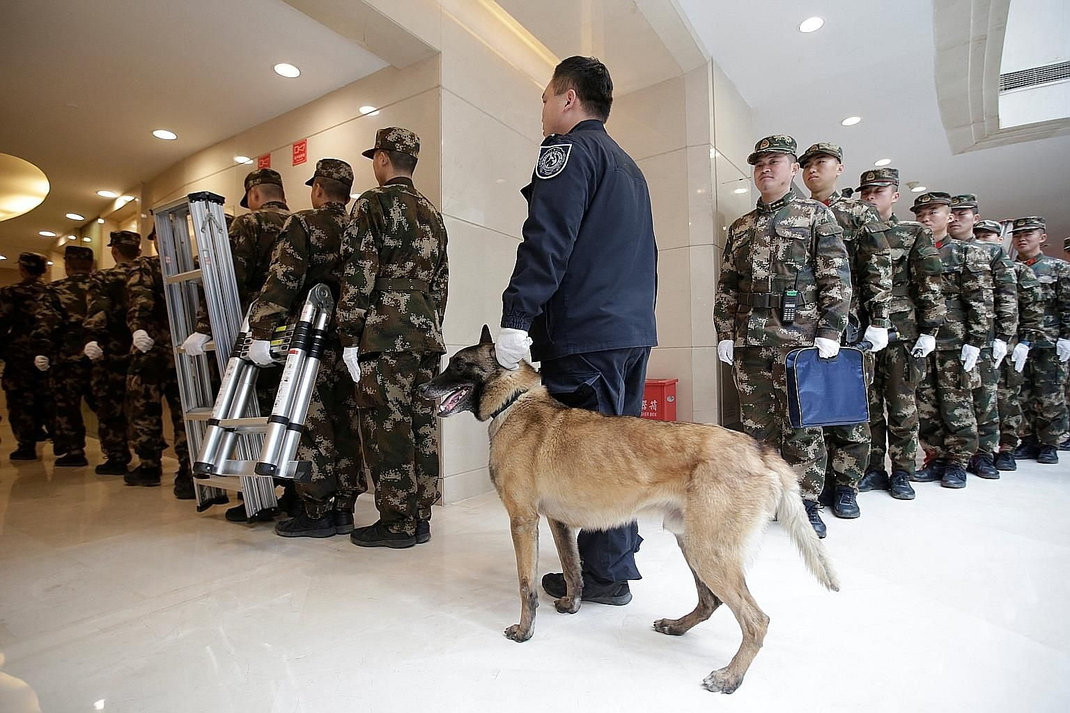 Paramilitary policemen waiting with a security dog outside the media centre for the Chinese People's Political Consultative Conference and the National People's Congress in Beijing yesterday.