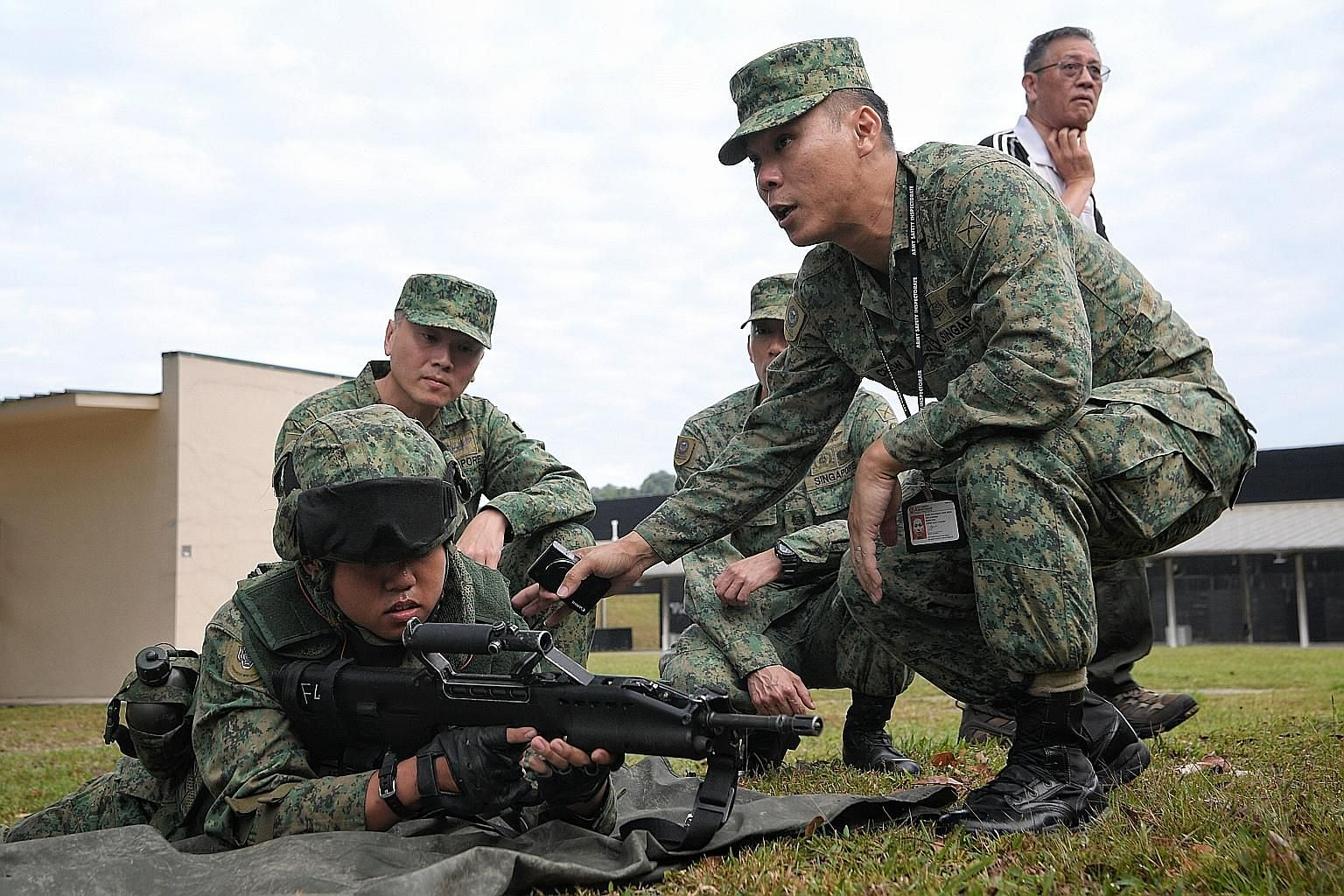 The Army Safety Inspectorate's Major Simon Chew (at right) carrying out an inspection observed by Singapore Armed Forces Inspector-General Tan Chee Wee (far left, behind) at Pasir Laba Camp on Thursday.
