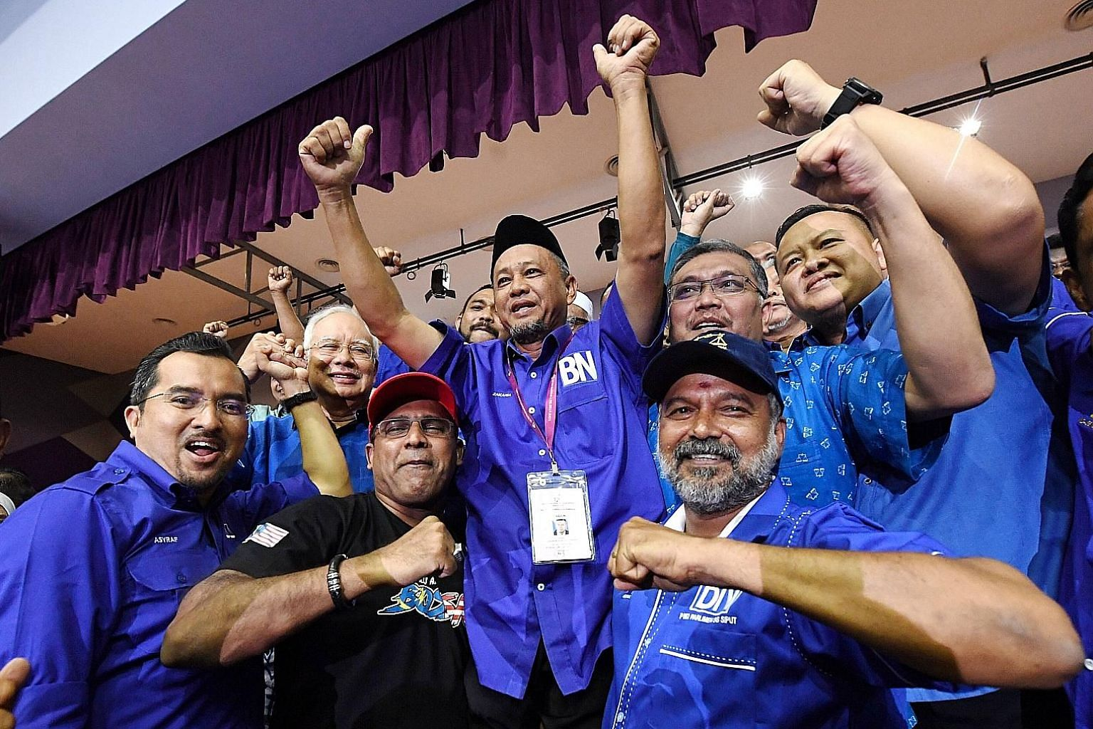 Above: BN's winning candidate, Mr Zakaria Hanafi (centre, shirt with BN logo), celebrating with former premier Najib Razak (second from left) and other party supporters yesterday. Left: PH's Mr Muhammad Aiman Zainali, who lost, casting his vote yeste