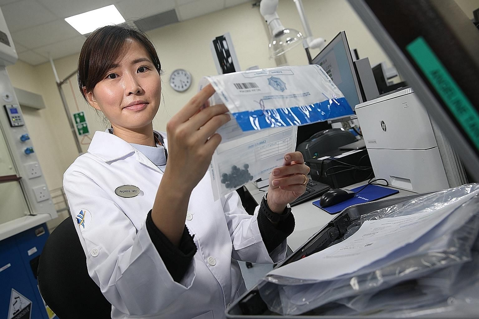 Ms Angeline Tang examining a drug exhibit at the Illicit Drugs Laboratory. Every day, about 50 laboratory staff decode the chemical make-up of seized drugs that they receive from CNB.