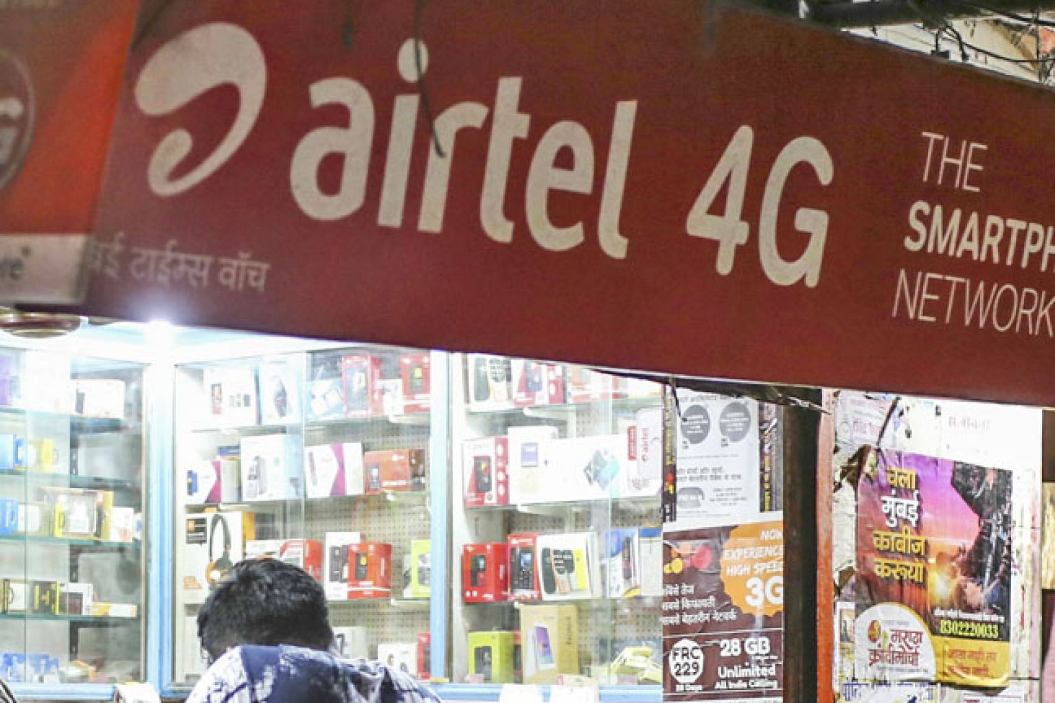 Bharti Airtel advertisements at a phone store in Mumbai, India. Bharti's fundraising exercise may affect Singtel's A1 credit rating.