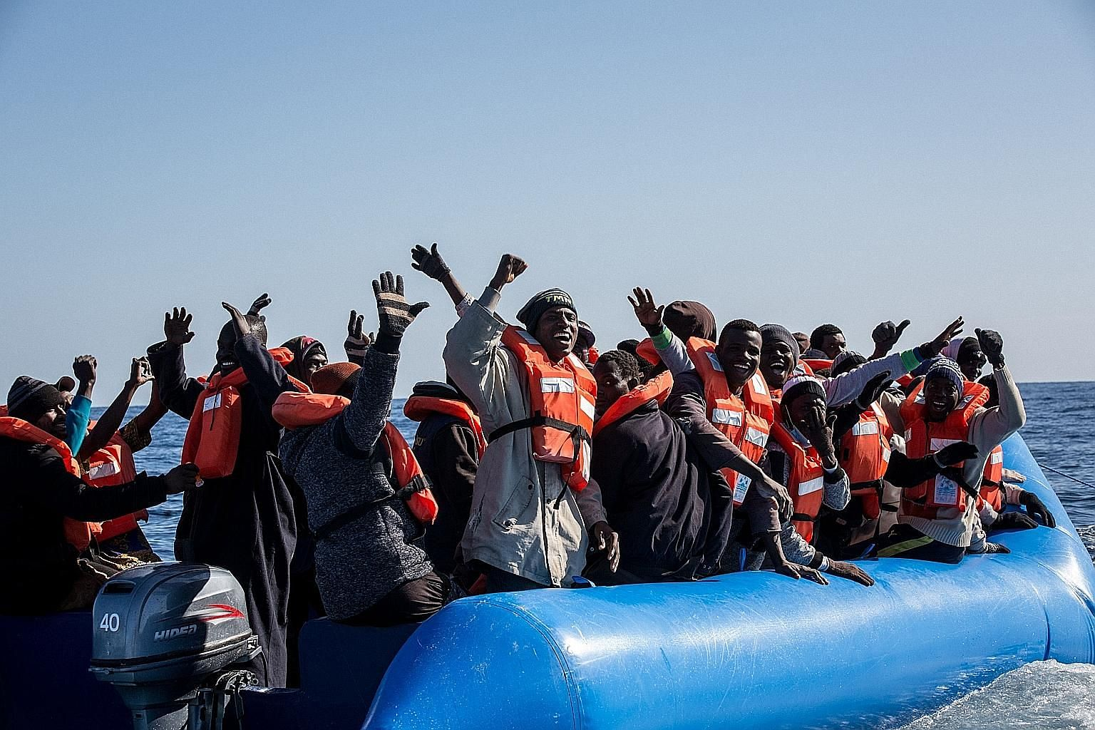 Migrants cheering their imminent rescue by a Dutch-flagged ship off Libya's coast in January. Most would-be asylum seekers know that if they succeed in setting foot in Europe, they have a high chance of staying and that in itself encourages further m