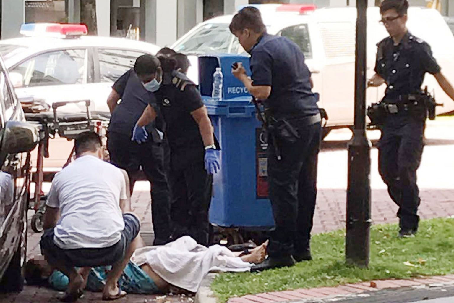 The accused's ex-wife being tended to by ambulance staff as she lay on the ground after the slashing in October 2016.