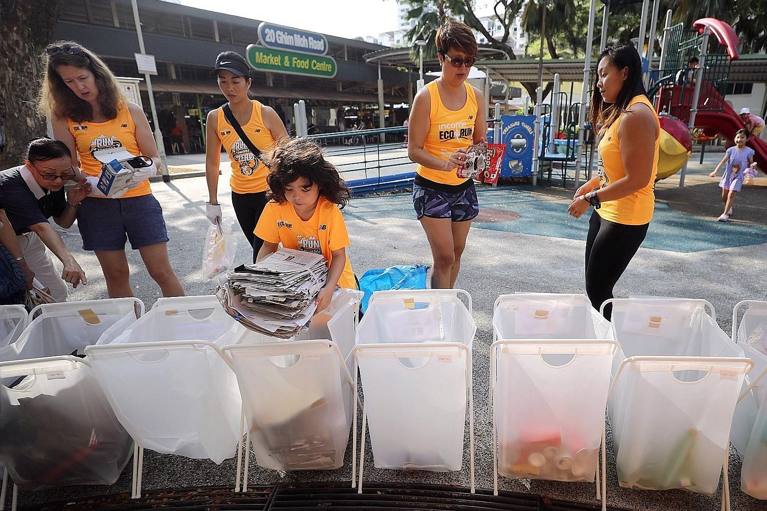 Seven-year-old volunteer Leni Vasu (left) placing newspapers into sorting bins, while Tzu Chi Foundation volunteers (above) sort out plastic items. All the items were contributed by the public at a collection point in Ghim Moh yesterday. Tzu Chi Foun