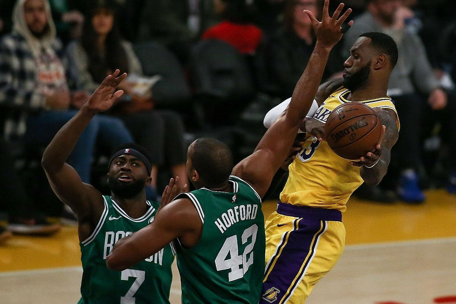 LeBron James double-teamed by Boston Celtics players Jaylen Brown and Al Horford at Staples Centre on Saturday. The Los Angeles Lakers lost 120-107 despite his triple-double.