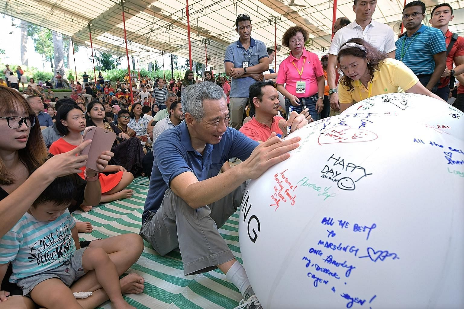 Prime Minister Lee Hsien Loong and Minister of State for National Development and Manpower Zaqy Mohamad penning their best wishes at the annual Marsiling Community Day yesterday, when the Marsiling Cares initiative was launched.