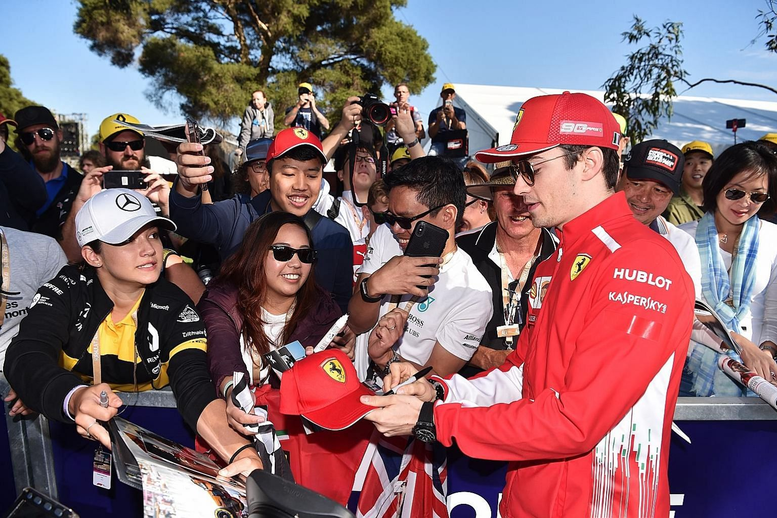 New Ferrari driver Charles Leclerc signing an autograph as he arrives at the Albert Park Grand Prix Circuit in Melbourne yesterday ahead of the season-opening Australian race.