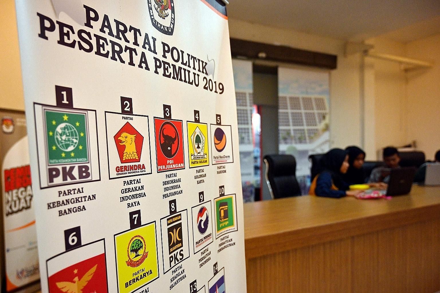 A poster in a General Elections Commission office in Jakarta showing the many political parties contesting the upcoming election. With the presidential race, voters now have to pore over at least five ballots.