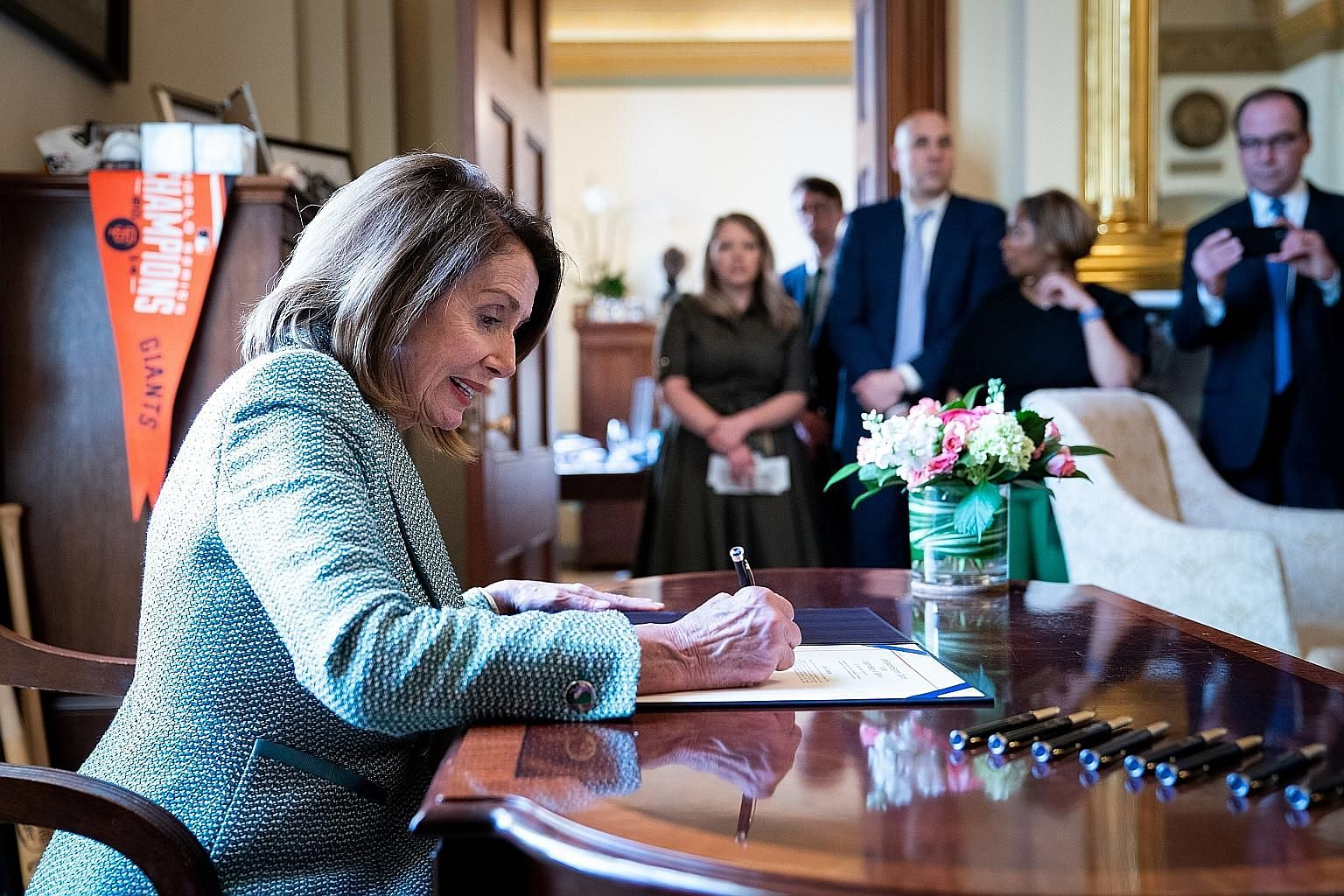 House Speaker Nancy Pelosi signing a disapproval resolution on March 14 on Capitol Hill in Washington blocking United States President Donald Trump's declaration of a national emergency.