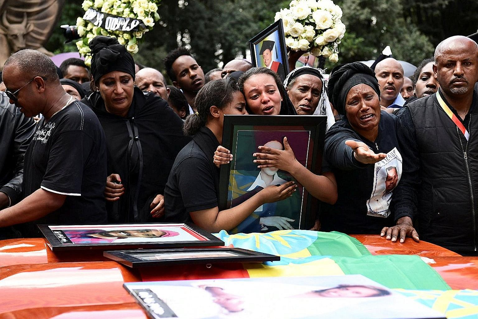 Relatives mourning next to empty coffins during a memorial service yesterday for victims of the Ethiopian Airlines crash.
