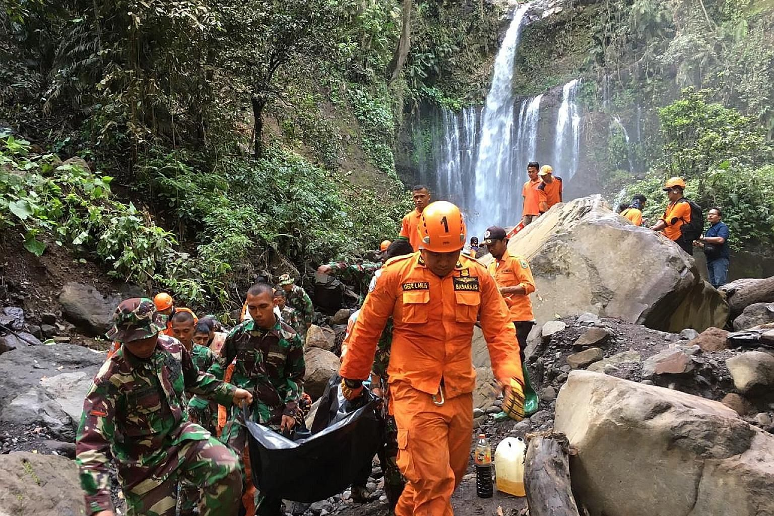 Rescuers carrying the body of Malaysian Lim Sai Wah, who died in a landslide triggered by an earthquake in Lombok on Sunday. Two other people died in the incident - another Malaysian and an Indonesian.