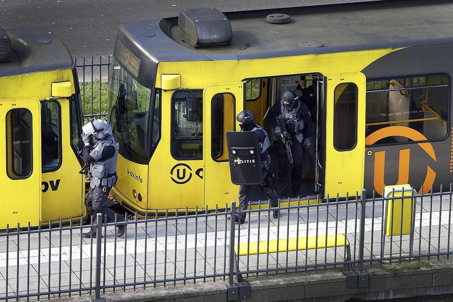 Dutch Special Police Forces inspecting the tram (top) yesterday after the attack, which the police believe was committed by a Turkish man named Gokmen Tanis (above).