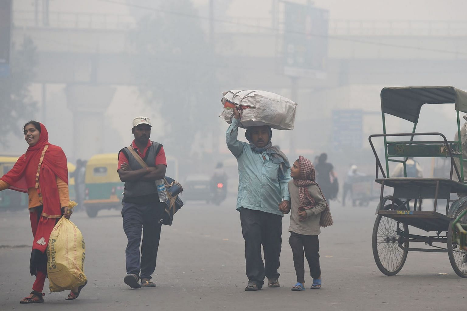 Above: A family looking for a rickshaw amid heavy smog in New Delhi, India's most polluted major city, last November. Right: A woman wearing a protective mask to fight the severe air pollution in Beijing in February. China and India have begun to pay