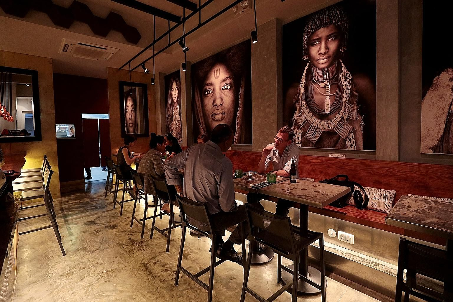The African-themed interior of Kafe Utu in Jiak Chuan Road features stunning paintings and intricately hand-carved doors.