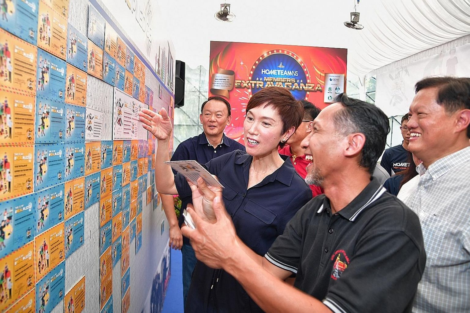 HomeTeamNS president Josephine Teo with two men who served in the Home Team previously, Mr Edwan Nizar Ahadan (foreground), 46, and Mr William Tan (in white), 62, looking at the pledges made by NSmen to reaffirm their commitment to serve and protect