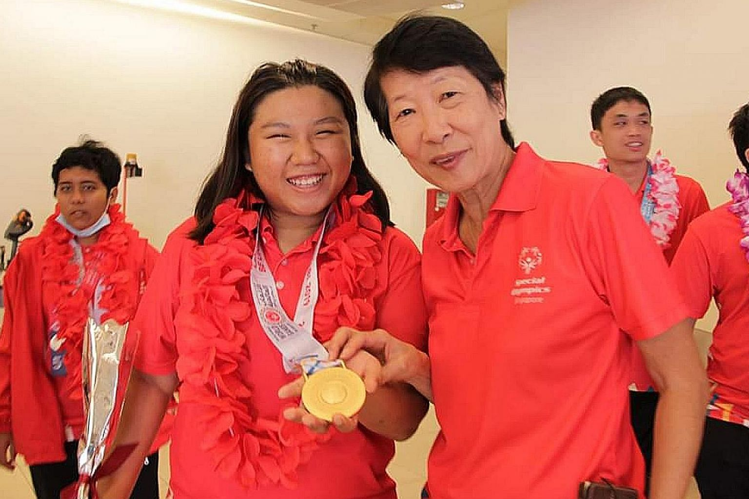 Soh Li Ning (far left) proudly presenting her bocce gold medal to Special Olympics Singapore president Dr Teo-Koh Sock Miang at Changi Airport yesterday, after returning from the Special Olympics World Games. The 30-strong Team Singapore won four gol