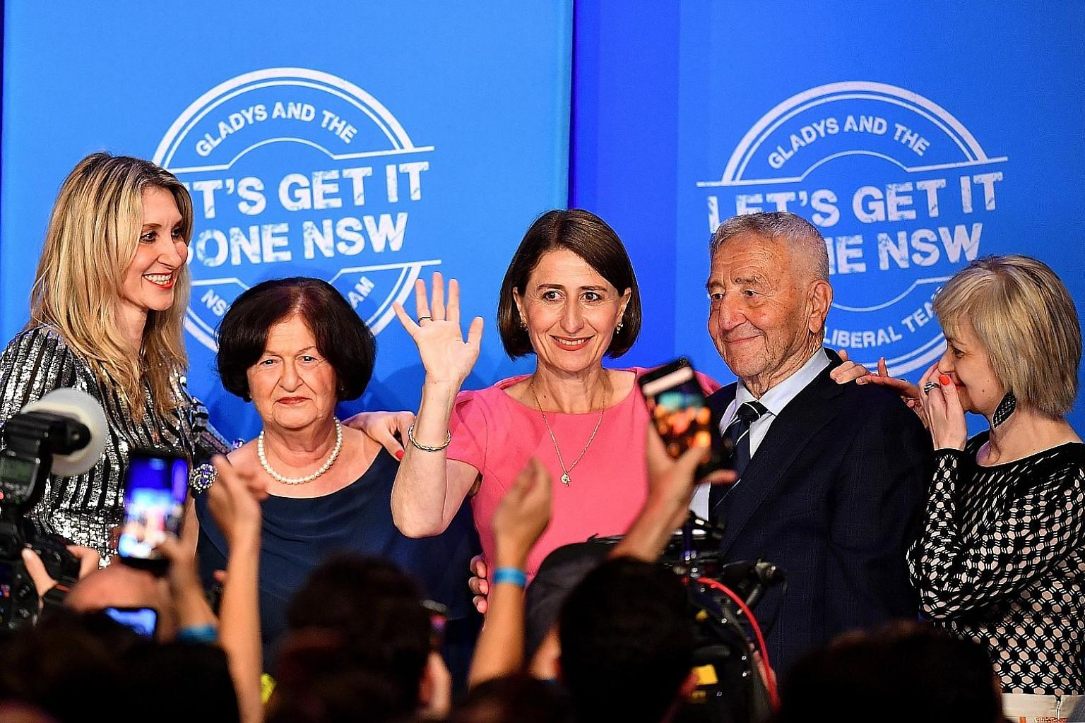 New South Wales Liberal leader Gladys Berejiklian (waving) celebrating her party's win at the New South Wales state election on Saturday, accompanied by her sister Mary (left), mother Arsha, father Krikorat and sister Rita (right).