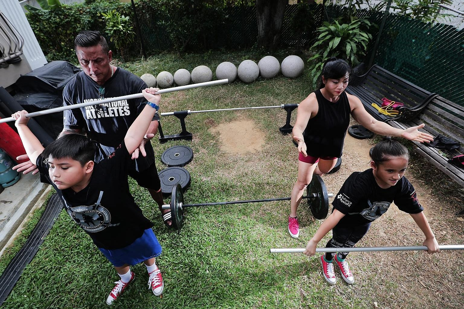 Mr Andrew Johnson and his wife Barbara Chng supervising their eight-year-old twins Brad and Ariel during training in the garden of their Katong home. A warm-up session, which involves mobility workouts and technique drills, is a must before the actua