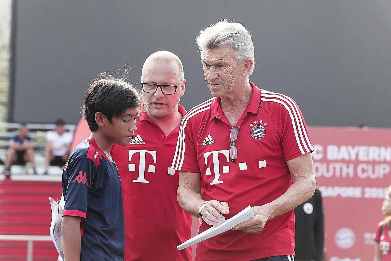 Bayern Munich great and World Cup winner Klaus Augenthaler (right), together with Sebastian Dremmler, head coach of Bayern's international programme, giving Nur Muhammad Asis Ijilrali some feedback at the FC Bayern Youth Cup Singapore finals yesterda