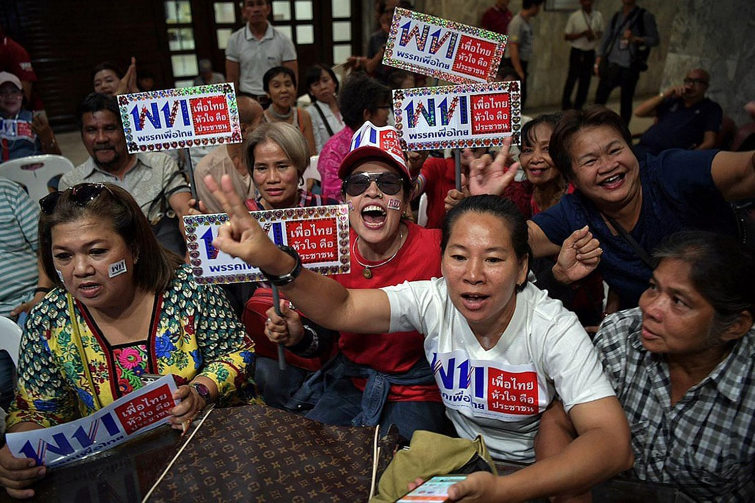 Supporters at the Pheu Thai headquarters in Bangkok reacting as results trickled in last night. It garnered seven million votes nationwide.