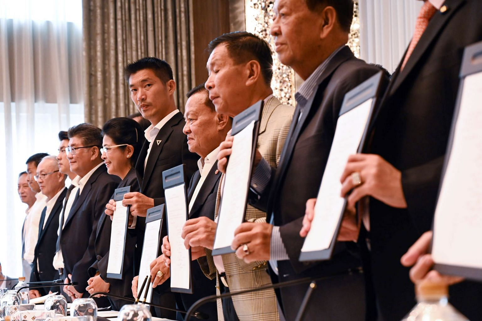 Leaders of different Thai political parties showing signed documents during a press conference in Bangkok yesterday. Several anti-junta parties formed a coalition in Thailand yesterday, vowing to thwart the pro-military Palang Pracharath Party in a bid to