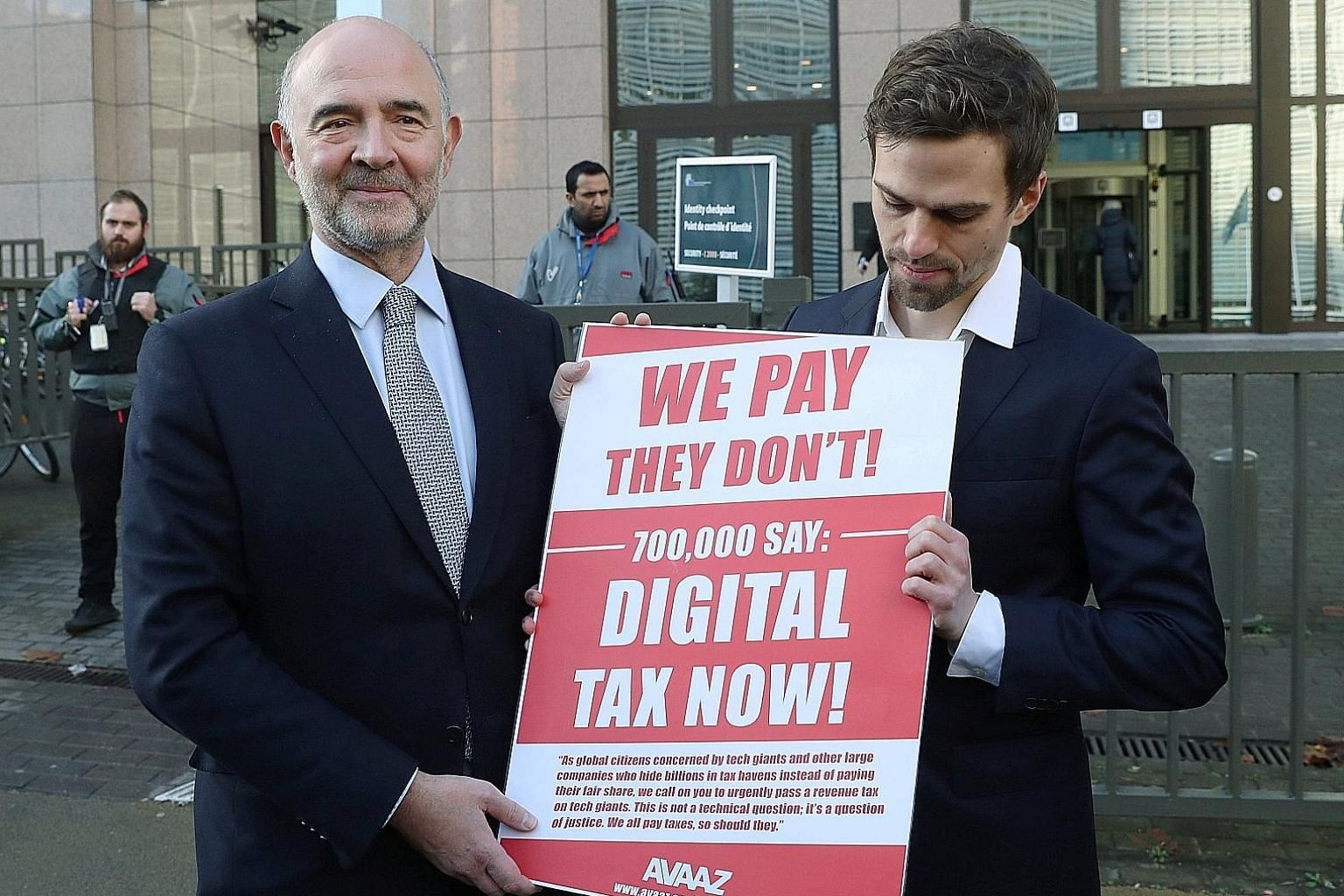 European Commissioner for Economic and Financial Affairs Pierre Moscovici (left) receiving a petition on digital tax from a representative of global activism group Avaaz outside the EU headquarters in Brussels, Belgium, last December. At the heart of