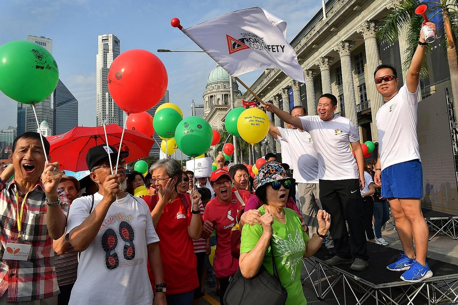 Senior Parliamentary Secretary for Home Affairs and for Health Amrin Amin (second from right) and Singapore Road Safety Council chairman Bernard Tay (on Mr Amrin's right) flagging off the 1.5km walkathon outside the National Gallery Singapore yesterd