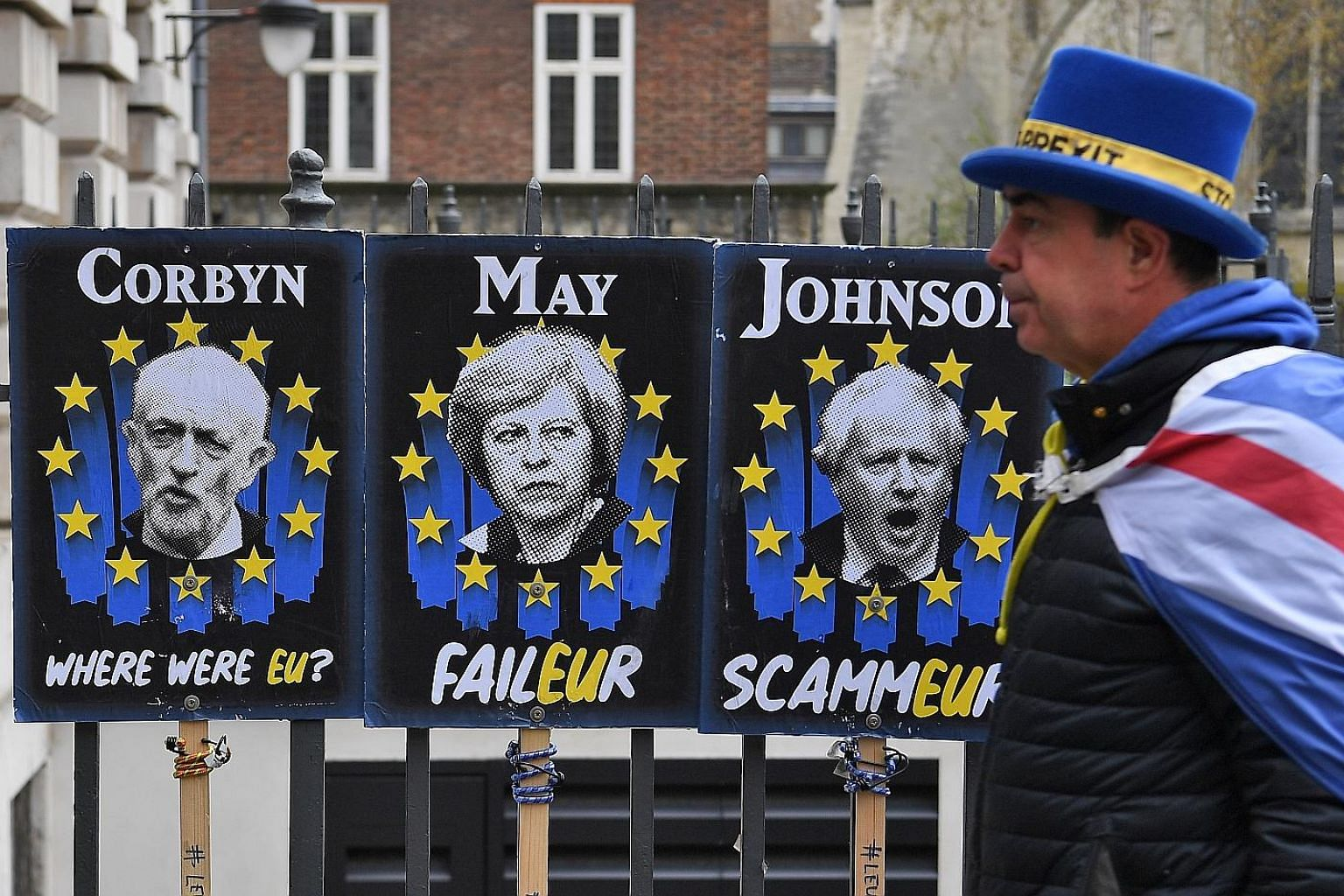 A pro-EU campaigner walking past posters mocking British politicians Jeremy Corbyn, Theresa May and Boris Johnson in London yesterday. A group of lawmakers will try and pass a law today that will force Prime Minister May to further delay Brexit. Barr