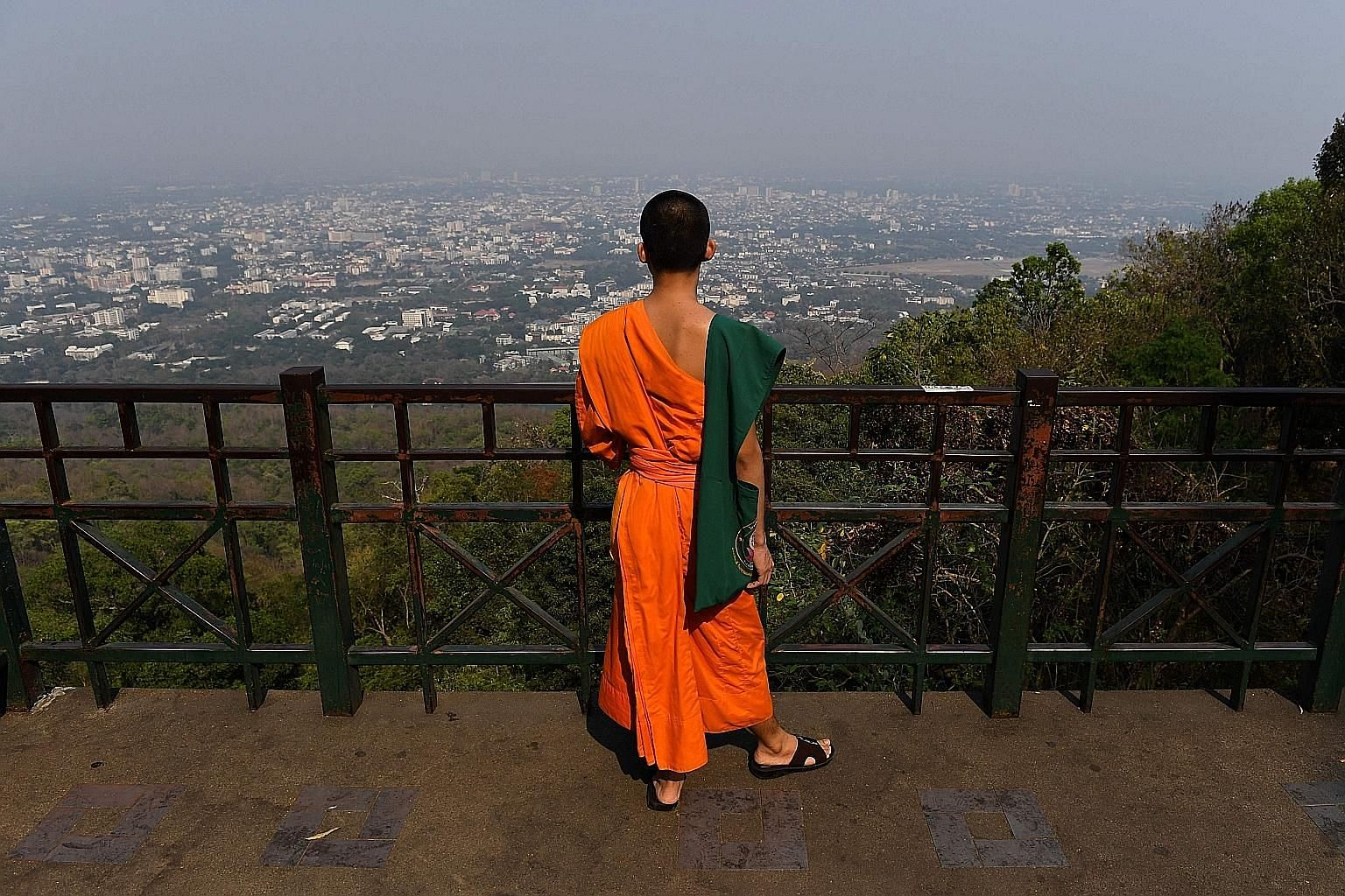 A novice Buddhist monk looking out over the smog-covered city in the northern Thai province of Chiang Mai yesterday.
