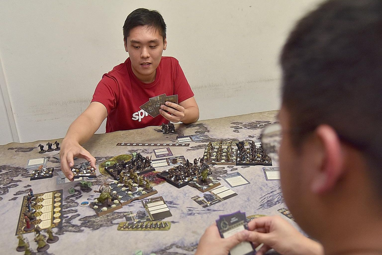Illustrator Russell Ng (far left), 29, a Game Of Thrones fan, playing the A Song Of Ice And Fire tabletop miniatures game at Gamersaurus Rex. The game, which launched six months ago after a successful Kickstarter bid, has tiny figures (above) that th