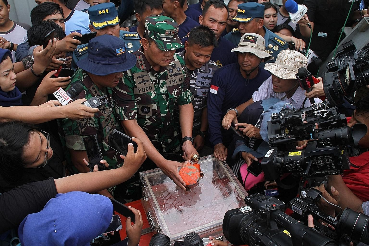 "Indonesian Navy personnel showing the cockpit voice recorder, the second ""black box"" from Lion Air Flight 610, after it was recovered on Jan 14. The new Boeing plane crashed into the sea last October."