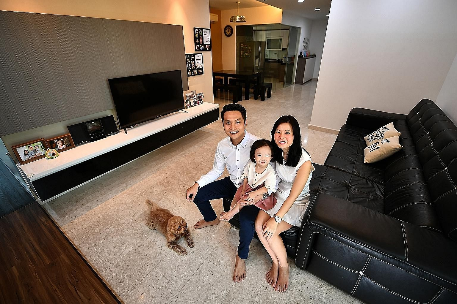 Mr Jason Tan, 38, senior associate executive director with OrangeTee & Tie, with his real estate agent wife Alice Loh, 37, and their daughter, Clariss Tan, two, in their 1,410 sq ft, three-bedroom condo in Modena in Simei.