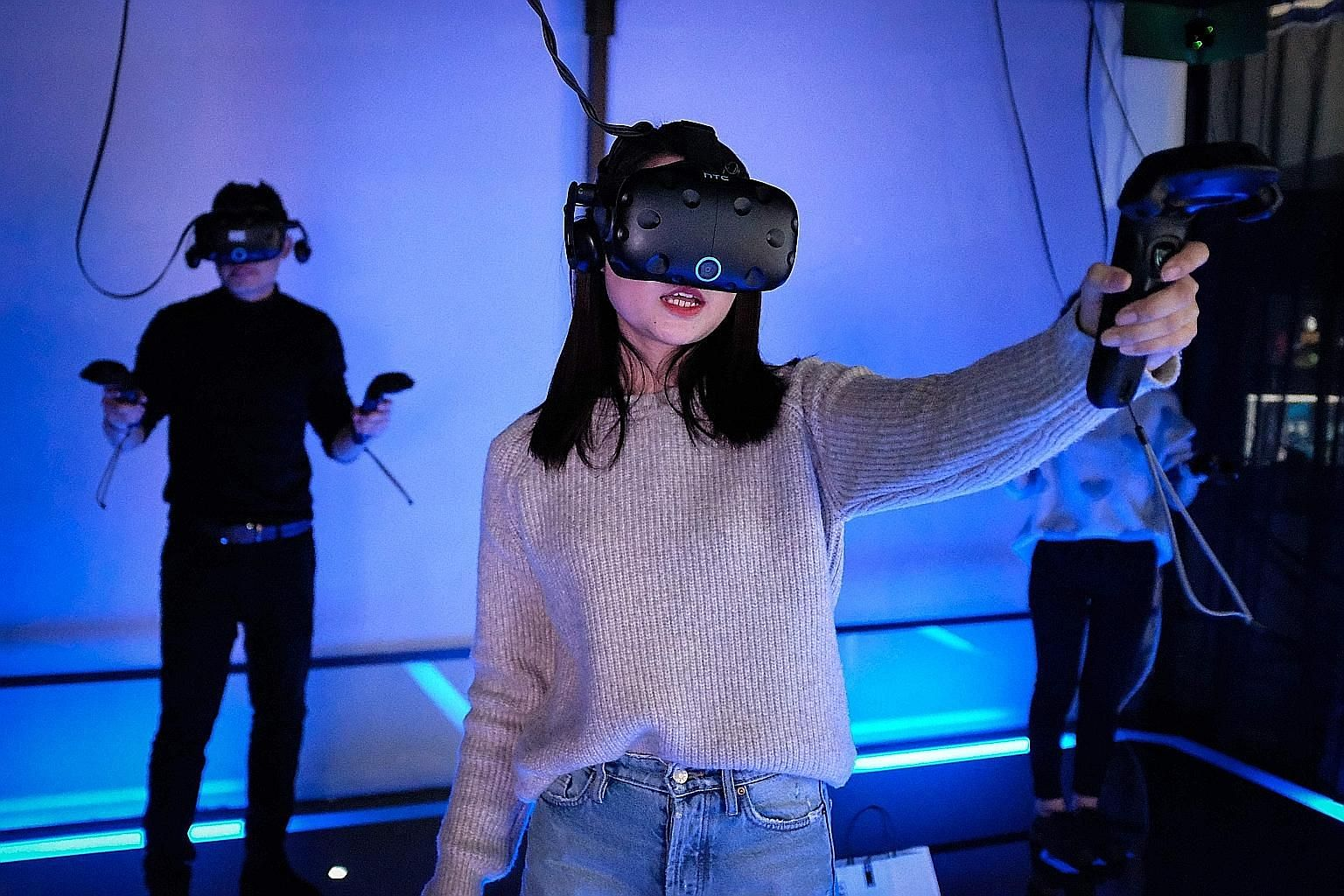 A woman using a virtual reality or VR headset to play games at a Shanghai arcade. China had an estimated 3,000 VR arcades in 2016, and the market could hit 5.25 billion yuan (S$1.1 billion) by 2021.