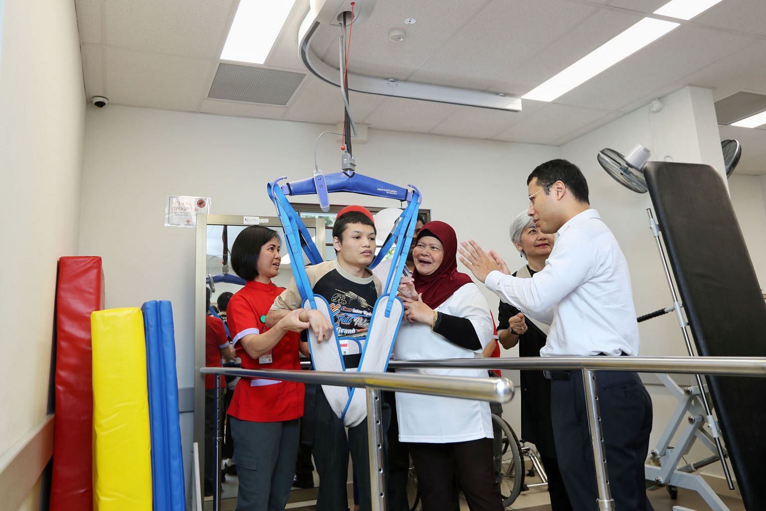 Mr Ahmad Fahmi Yusuf trying out a mechanical hoist in the new Day Activity Centre in Jurong West as Mr Desmond Lee, Minister for Social and Family Development, looks on.