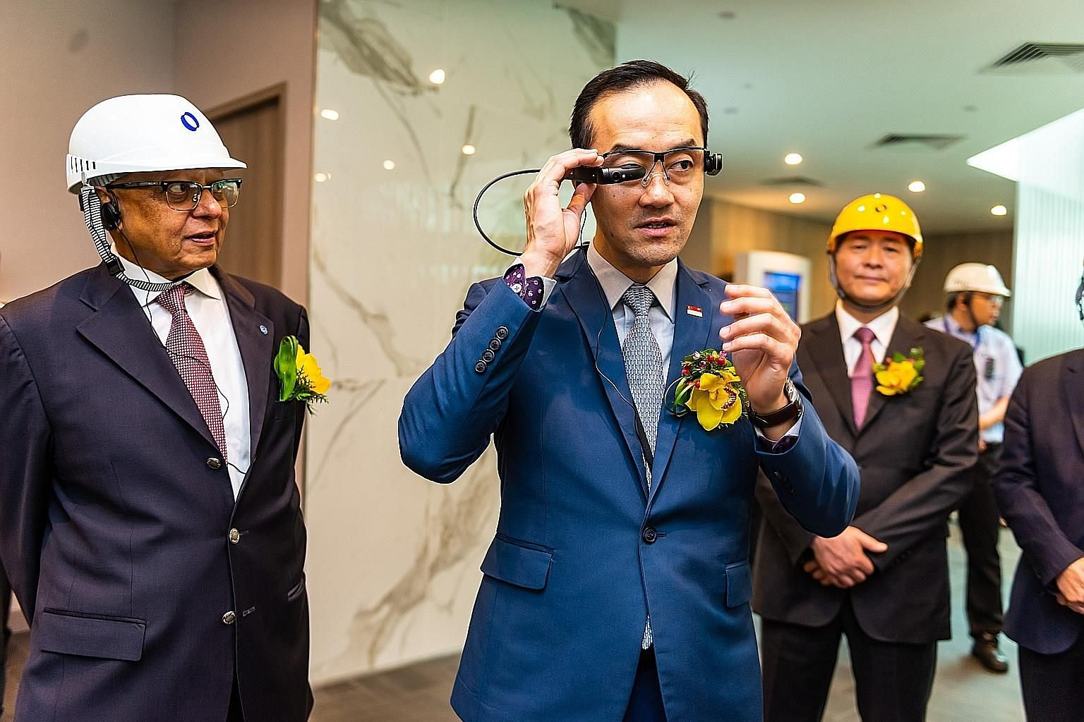 Senior Minister of State for Trade and Industry Koh Poh Koon trying out Makino Asia's Smart Glasses, which provide real-time information to engineers on the ground who are trying to fix technical faults in machines. On his left is Mr K. S. Sankaran,