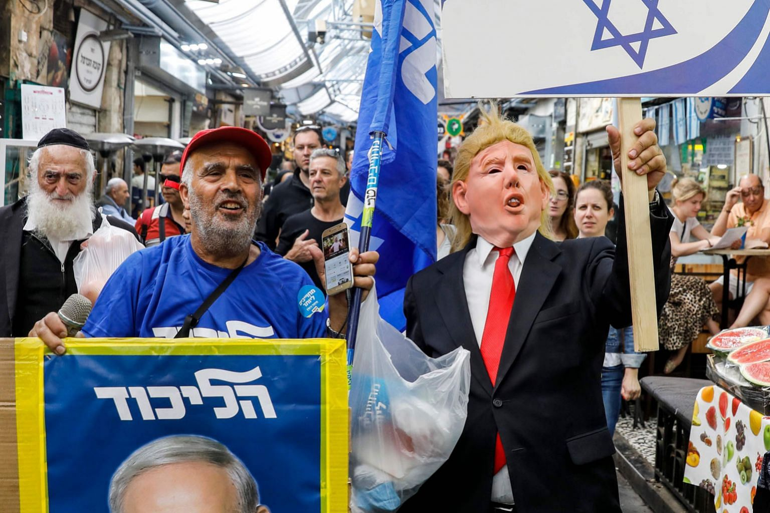 "A Netanyahu supporter wearing a Trump mask marching with a sign reading in Hebrew ""Guardian of Israel"" along with another carrying the portrait of the Israeli leader during a poll campaign on Sunday.PHOTO: AGENCE FRANCE-PRESSE"