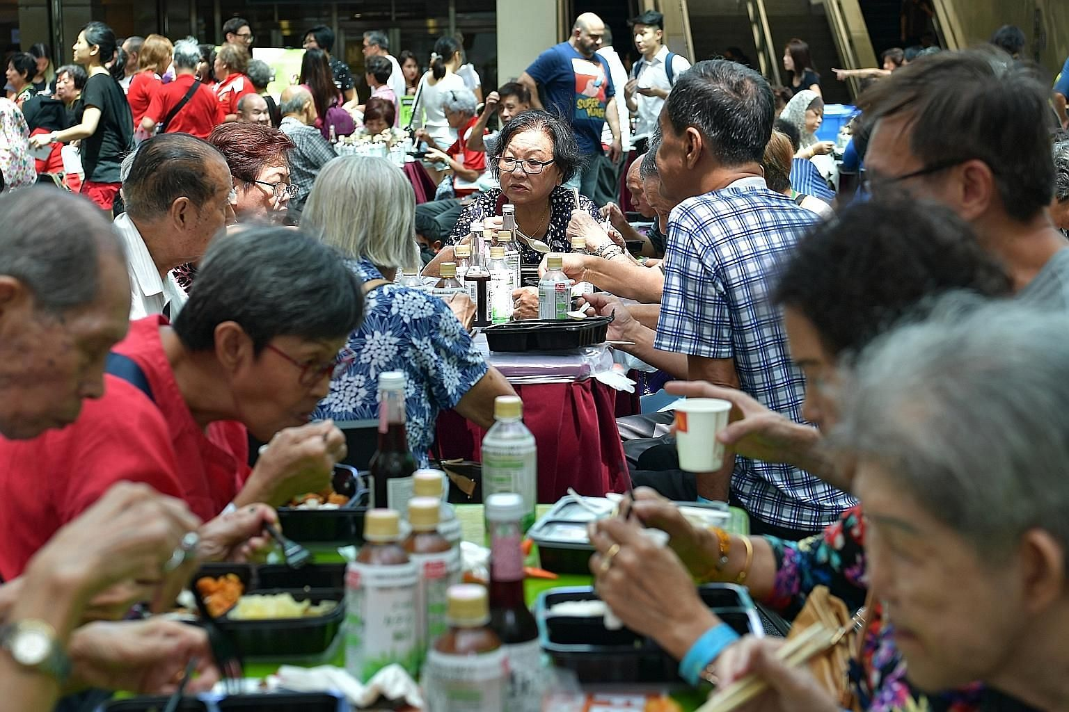 People tucking into a meal at Food Bank Singapore's inaugural community engagement event yesterday at City Square Mall in Kitchener Road. The day's activities included cooking demonstrations and talks on food insecurity and food waste. There were als