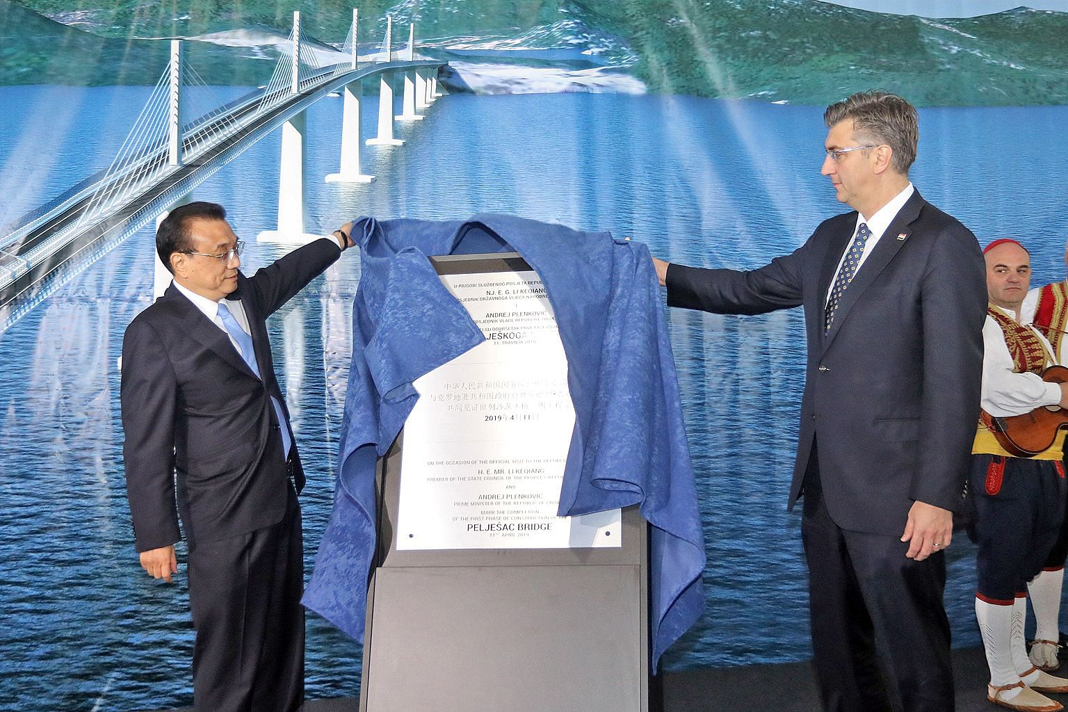 Chinese Premier Li Keqiang and Croatian Prime Minister Andrej Plenkovic unveiling a plaque to mark the completion of the first phase of construction of the Peljesac Bridge, which is being built by a Chinese company, in Brijesta, Croatia, on Thursday.
